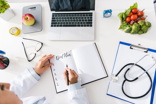 overhead view of nutritionist writing in notebook near laptop