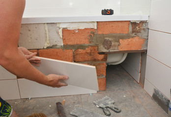Bathtub installation and tiliing with white ceramic tiles in house bath room