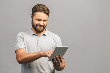 Happy bearded young man in casual standing and using tablet isolated over grey background.