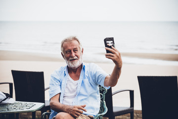 Elderly Caucasian men using mobile phones By using the video call application to talk to his friend, while sitting and resting on the beach on vacation, to retriement age concept.