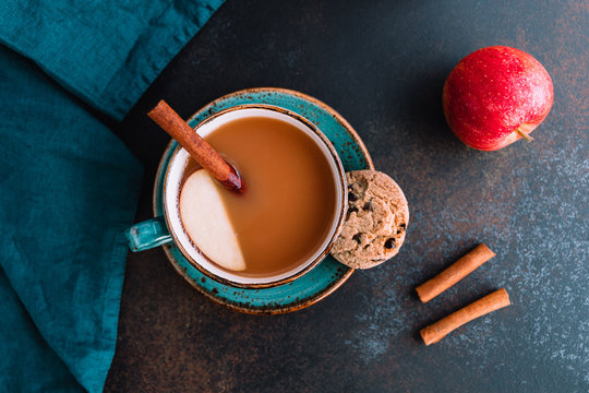 Wintertime chai-spiced apple cider with assam tea, cinnamon, ginger, cardamom and almond milk. Christmas or Thanksgiving cozy flat lay.