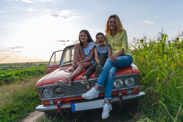 Family vacation, mom with theyr teen children all in casual clothes sitting together on a hood of the retro car among the field, all are happy and smiling Fototapete