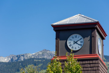 Roman Numeral Clock Tower with rocky mountains and blue sky in the background.