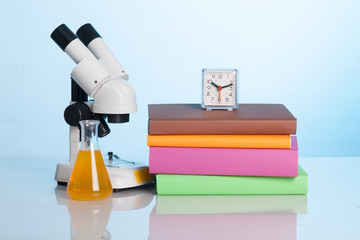 Books and a microscope on the desk of the student