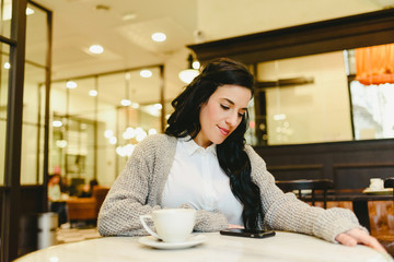Pretty brunette woman checking her smartphone while having breakfast drinking coffee in a retro restaurant.
