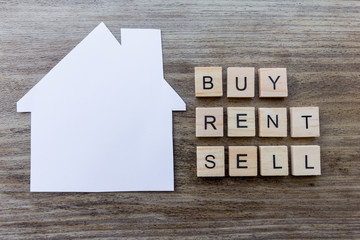 Housing Market Concept - Paper house with the words 'Buy, Rent, Sell'