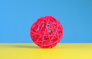 Red spherical mesh ball on multicolored background