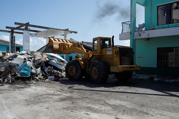 A worker in a bulldozer cleans debris from the parking lot of a private shopping center after Hurricane Dorian hit the Abaco Islands in Marsh Harbour