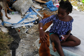 A girl pets her dog after Hurricane Dorian hit the Abaco Islands in Spring City