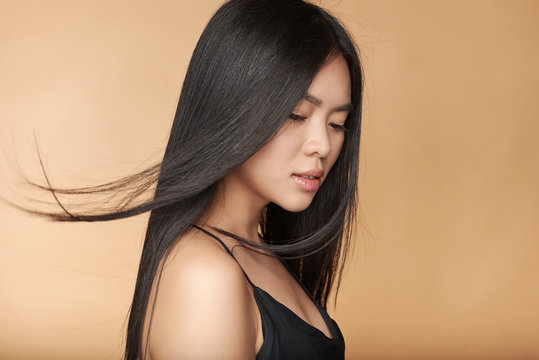 A young beautiful asian girl dressed in a black dress with natural makeup and shiny hair in the wind stands on a beige yellow natural background. Cosmetics concept. Shampoo.