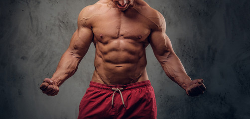 Muscular man with nice muscules is posing for photographer at dark photo studio.