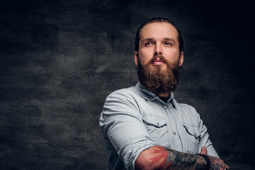 Groomed bearded man with tattooes is posing at dark photo studio.