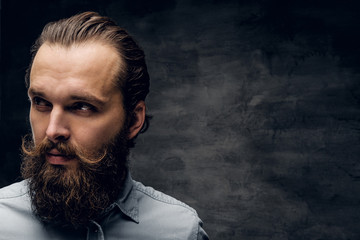 Groomed bearded man in light shirt is posing at dark photo studio.