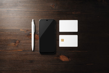 Corporate identity template on wooden background. Smartphone, business card, bank card and pen. Top...