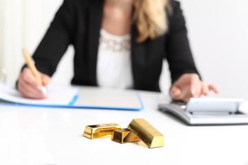 Frau mit Goldbarren und Taschenrechner