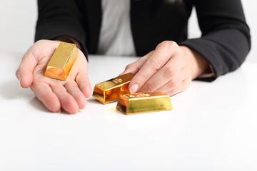 Frau präsentiert Goldbarren