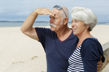 happy senior adult couple tourists looking at something