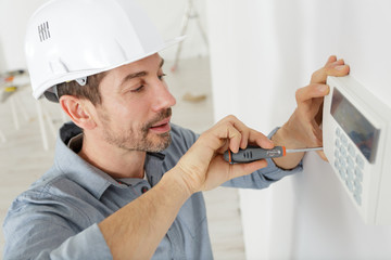 a happy plumber fixing thermostat