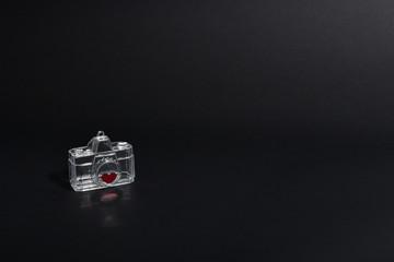 cámara fotográfica transparente en fondo negro con corazon rojo y reflejo