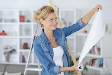 woman with roll of wallpaper