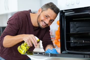 portrait of man spraying product to clean oven