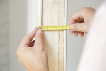 Man holding a meter, measuring dimensions on plasterboard panel - DIY home improvement concept