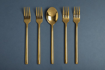 Flat lay composition with gold cutlery on grey background