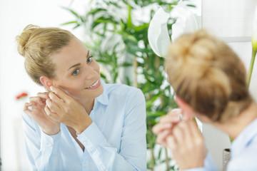 a beautiful woman putting earring