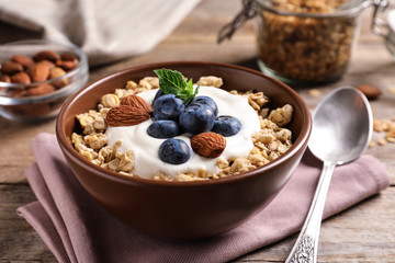 Bowl of tasty oatmeal with blueberries and yogurt on wooden table