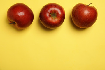 Flat lay composition with ripe juicy red apples on yellow background, space for text