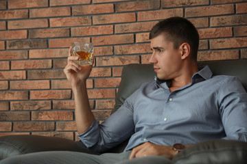 Young man with glass of whiskey near brick wall indoors
