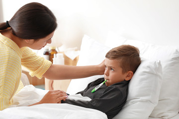 Mother measuring temperature of her sick son in bed