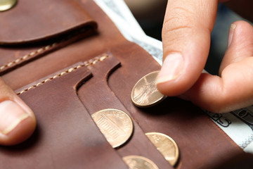 Young woman putting coin into wallet, closeup