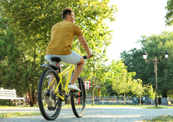 Handsome young man with bicycle in city park