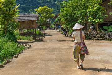 Women are walking at Phia Thap community based tourism a handicraft rural village from the Nung ethnic minority is surrounded with green rice paddy fields and karst Mountains
