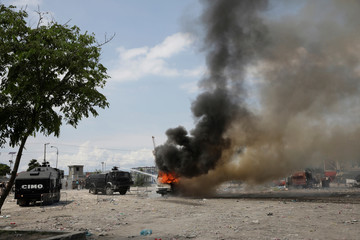 Haitian National Police (PNH) extinguish a burning police bus during a protest outside the facilities of the Parliament and the Senate in Port-au-Prince