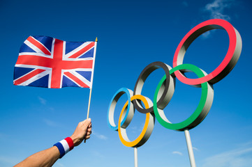 RIO DE JANEIRO - MARCH, 2016: Hand of a supporter wearing red white and blue sweatband holds a UK flag in front of Olympic Rings.