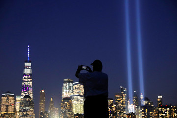 The Tribute in Light is lit in New York City to commemorate the 18th anniversary of September 11, 2001 attacks as a man photographs them from Liberty State Park, New Jersey