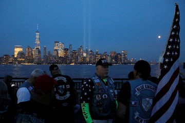 Members of the Blue Knights, a motorcycle club made up of active and retired law enforcement members, gather to view the Tribute in Light on the 18th anniversary of the September 11, 2001 attacks, from Liberty State Park, New Jersey
