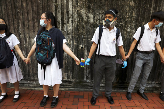 Secondary school students hold a Pepe the Frog plush toy with an eye patch as they form a human chain during a demonstration in Hong Kong