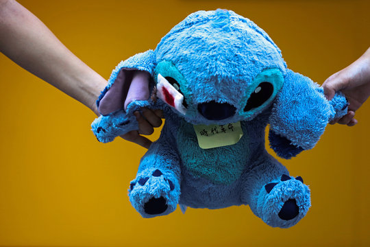 Secondary school students hold a Stitch plush toy with an eye patch as they form a human chain during a demonstration in Hong Kong