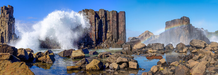 Panorama of waves breaking over basalt rock formations creating a rainbow over rockpools at Bombo Headland quarry, New South Wales coast, Australia Wall mural