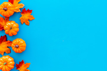 Autumn background with leaves and pumpkins on blue top view space for text frame