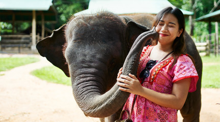 female thai tourist posing with elephant at sanctuary making funny expression