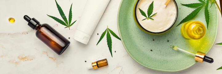 Cosmetics with cannabis oil on a turquoise plate on a light marble background. Copy space, mockup. Banner