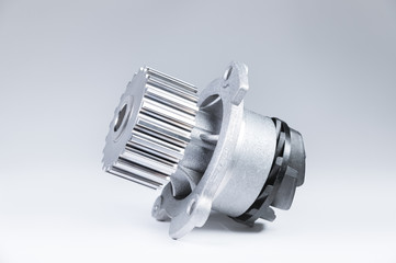 New metal automobile pump for cooling an engine water pump on a gray background with a gradient. The concept of new spare parts for the car engine