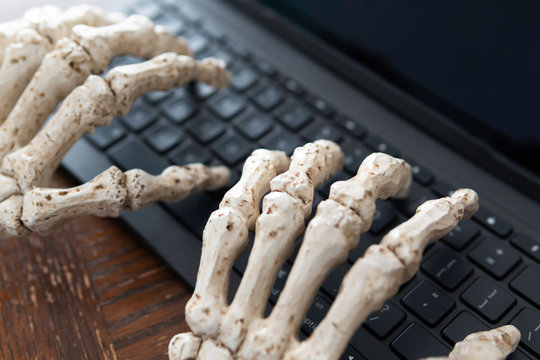 Skeleton hands typing a report using a keyboard - Halloween Concept