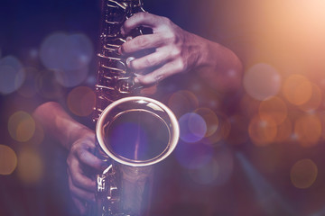close up of saxophone player plays saxophone  with music concert light and Bokeh on stage