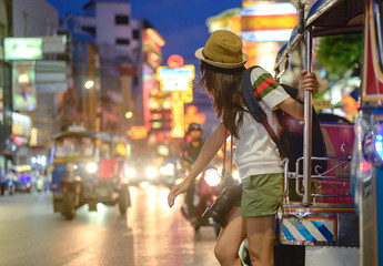 woman tourist standing at street side calls motor tricycle, local transport services in Chinatown of Bangkok, Yaowarat famous and popular place with street food for tourist