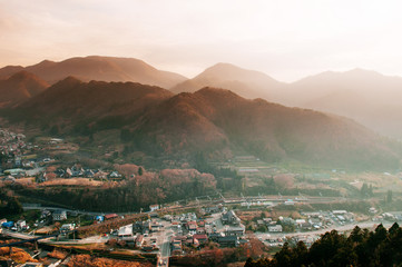 Yamadera town in mountain valley under evening sunlight through foggy atmosphere, Yamagata - Japan